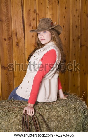 A woman sitting on a hay bale with her hat on while holding a horses bridle and with a serious look on her face. - stock photo