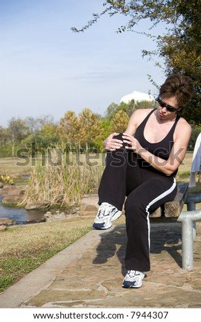 A woman sitting on a park bench grasping her knee as if injured. - stock photo