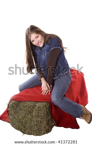 A woman sitting on a red blanket on a hay bale in denim with a simile on her face. - stock photo