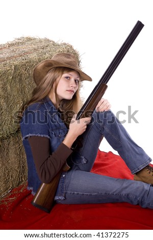 A woman sitting on a red blanket with denim and a hat on with a serious expression while holding a gun. - stock photo