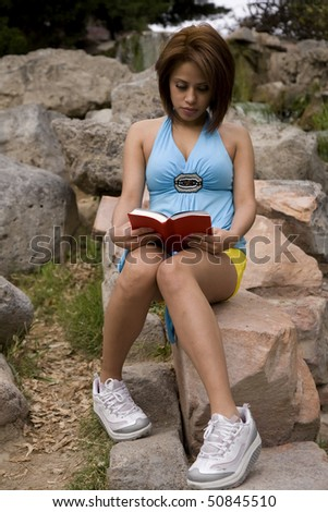A woman sitting on a rock in a park studing from a book.