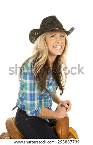 a woman sitting on a saddle in her cowgirl hat with a big smile on her face. - stock photo