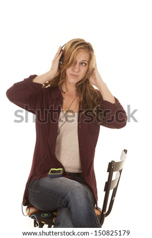 A woman sitting on a stool listening to music.
