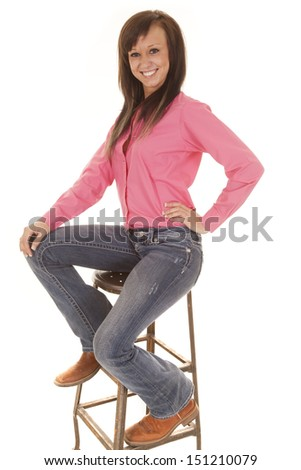 a woman sitting on a stool with a smile on her face.