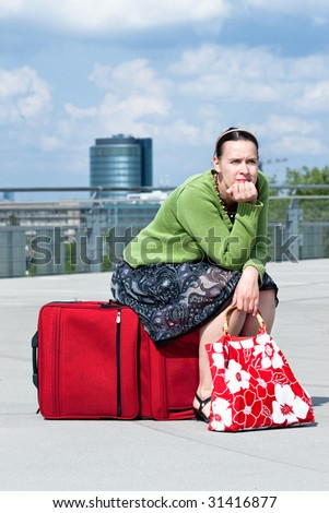 A woman sitting on a suitcase in an urban setting.