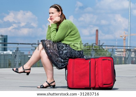 A woman sitting on a suitcase outdoors in an urban setting.