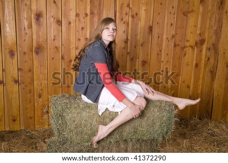 A woman sitting on hay bale with bare feet with a small smile on her face. - stock photo
