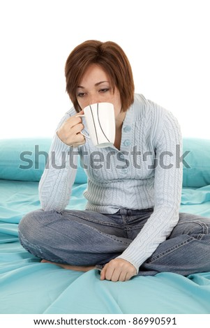 A woman sitting on her bed half asleep holding and drinking her coffee from a cup. - stock photo