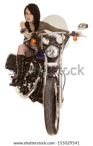 A woman sitting on her bike with a serious expression in her boots and fish net stockings. - stock photo