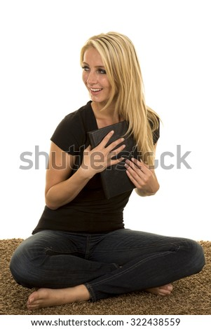 A woman sitting on her carpet holding her book to her chest with a smile. - stock photo