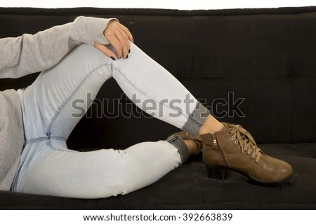 a woman sitting on her couch in her jeans with her boots on the couch. - stock photo