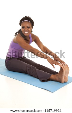 a woman sitting on her mat stretching out her legs with a smile on her face. - stock photo