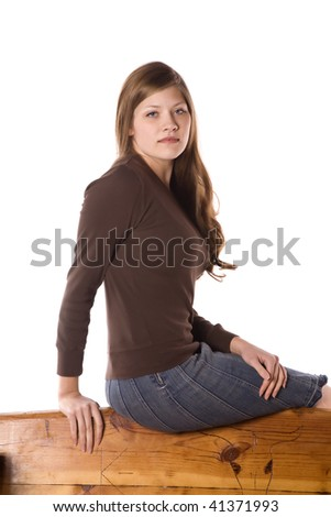 A woman sitting on the back of a bench with a serious look on her face. - stock photo