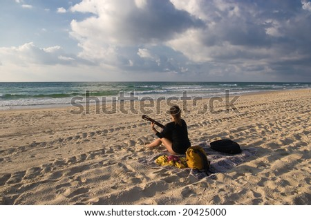 a woman sitting on the beach and playing guitar - stock photo