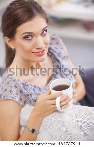 A woman sitting on the couch with a cup in her hands - stock photo