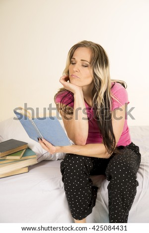 A woman sitting on the edge of her bed reading a book, in her pajamas - stock photo