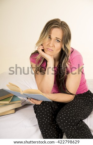a woman sitting on the edge of her bed with an upset expression on her face. - stock photo