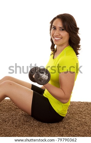 A woman sitting on the ground lifting her weights.