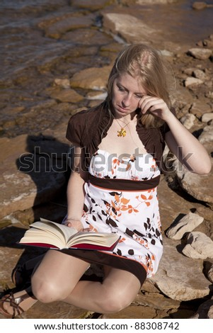 a woman sitting on the rocks reading a very sad books. - stock photo