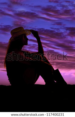 A woman sitting with a beautiful sky behind her holding on to the brim of her hat.