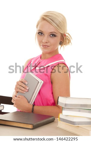 A woman sitting with her book up to her chest and a small smile on her lips