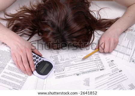 A woman slumped over in despair on a pile of tax forms. - stock photo