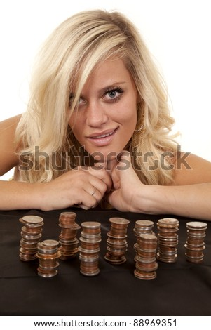 A woman smiling after stacking a bunch of her change. - stock photo