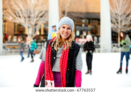 A woman smiling at an outdoor ice rink - stock photo