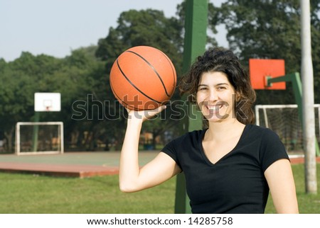A woman smiling for the camera with a basketball court in the background, holding a basketball in one hand. - horizontally framed - stock photo