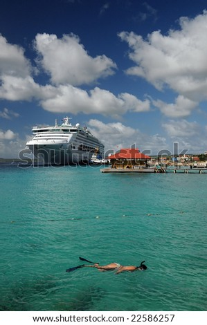 A woman snorkels near a cruise ship - stock photo
