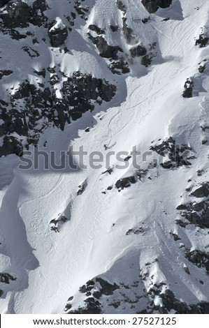 a woman snowboard competitor having made a jump over a rock cliff makes turns down a very steep corridor in the 2009 extreme freeride world championship finals - stock photo