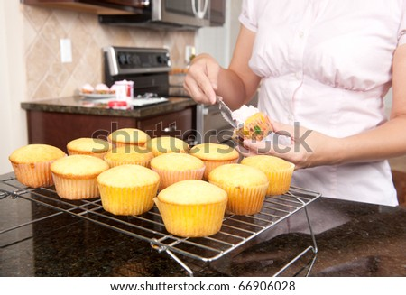 A woman spreads icing over a cupcake before starting on a new batch.  Focus is on middle row of cupcakes.
