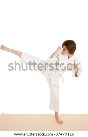 A woman standing and doing a kick  showing her anger. - stock photo