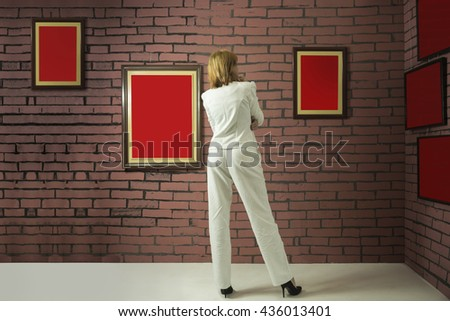 A woman standing and looking at blank of one color frames in art gallery or museum. Wall of bricks and frames are painted in red colors