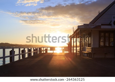 A woman standing at a pier in Russell, New Zealand, looking into the distance at sunset - stock photo