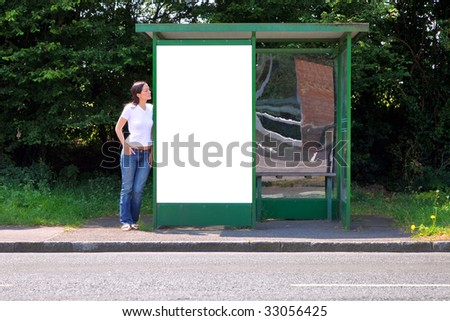 A woman standing at a rural bus stop leaning on a shelter with a blank billboard, clipping path included for you to add your own message in the space. - stock photo