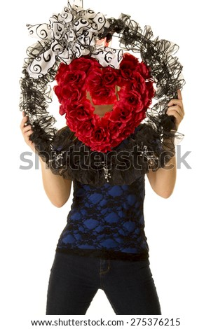 a woman standing behind a heart wreath with her face covered. - stock photo