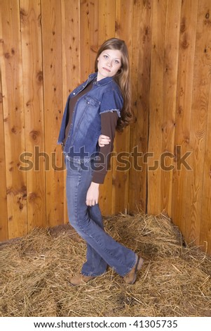 A woman standing by a wood wall with a denim shirt on holding her arms behind her with a serious look on her face. - stock photo