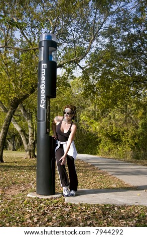 A woman standing by an emergency call box holding her knee as if in pain. - stock photo