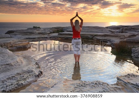 A woman standing by the ocean at sunrise, practicing yoga, meditation, pose.  Rejuvenating the soul, quiet time and solitude in natures beautiful surrounds.