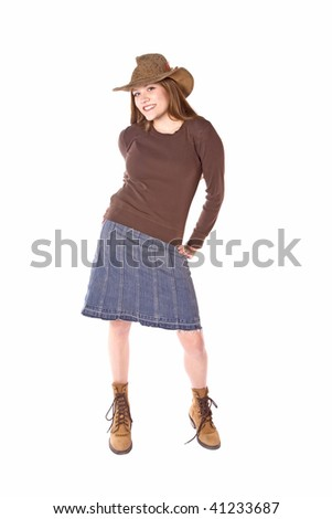 A woman standing in a denim skirt with a hat on and with a smile on her face. - stock photo
