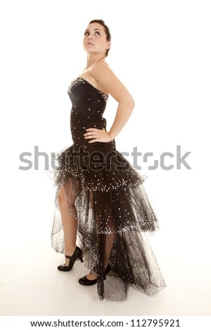 a woman standing in her black formal sparkling gown looking up with her eyes. - stock photo