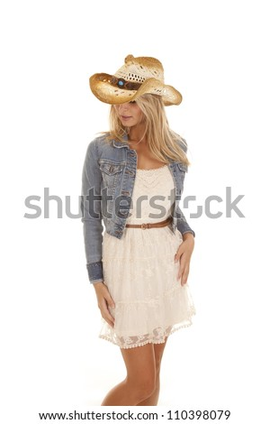 A woman standing in her dress, denim jacket, and hat looking down. - stock photo