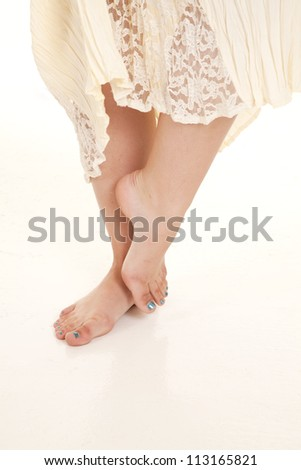 A woman standing in her lace dress showing off her feet. - stock photo