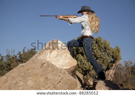a woman standing in her western wear in the outdoors holding a gun. - stock photo