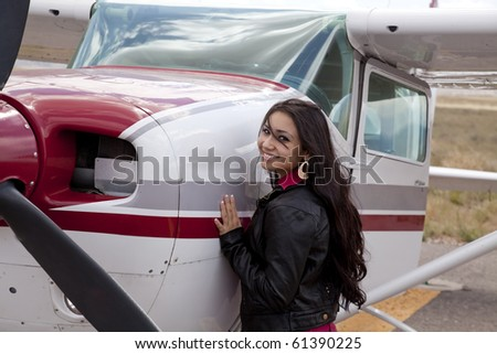 A woman standing next to a small airplane. - stock photo