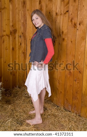 A woman standing next to a wood wall in the hay with her bare feet in a white skirt with a small smile, - stock photo