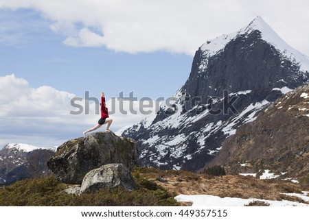 A woman standing on a rock in mountains practicing yoga