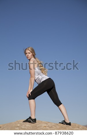 A woman standing on a rock stretching out her legs. - stock photo