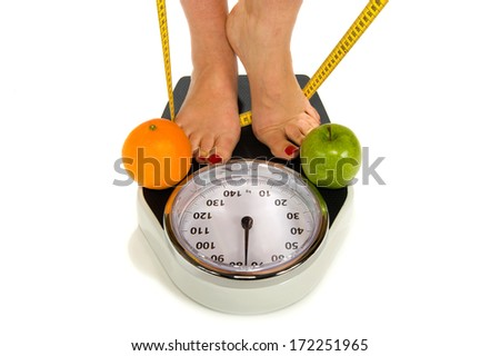 A woman standing on a weight scale with measuring tape and fruit - stock photo